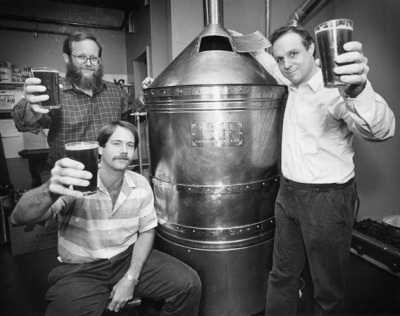 Three men holding full beers in toast around a copper brewing kettle