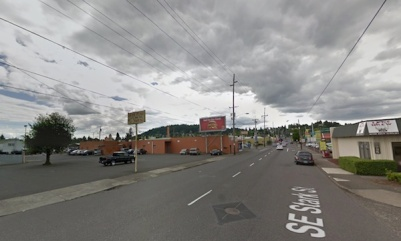 The intersection of Stark & 82nd, Portland, OR showing wide streets, low-slung buildings, lots of parking, some hills in the distance