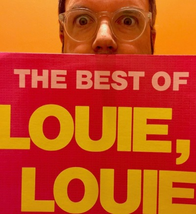 "man holding a copy of ""The Best of 'Louie, Louie'"" vinyl album"